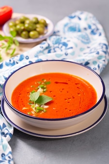 A plate of traditional spanish gazpacho with tomato, pepper, garlic and tabasco sauce with olives and basel leaf