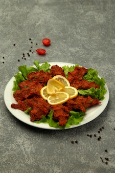 Plate of turkish chig kofte raw meatball with tomato paste and spice