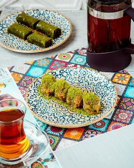 A plate of turkish dessert with layered dough and pistachio