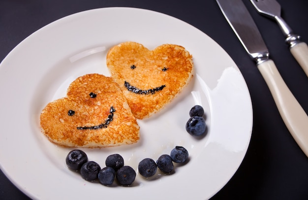 Plate of two pancakes in the shape of heart with berries on white table