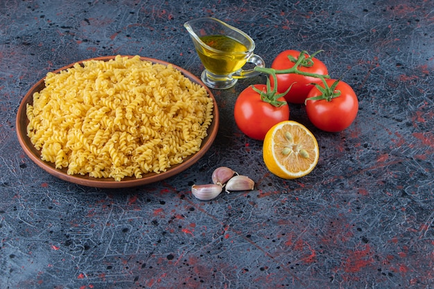 Un piatto di pasta a spirale cruda con olio e pomodori rossi freschi su uno sfondo scuro.