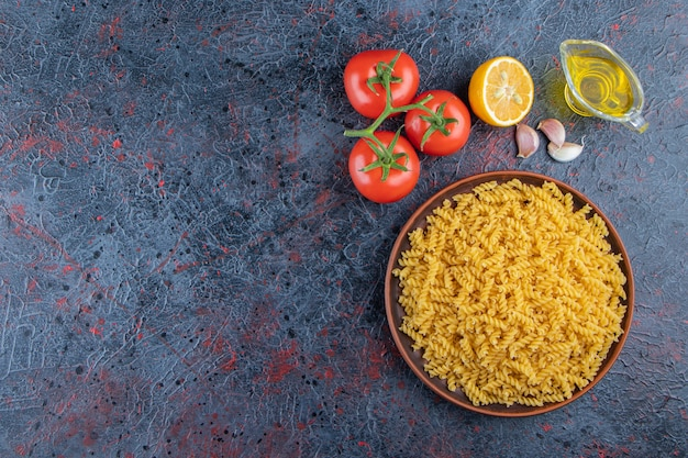 A plate of uncooked spiral pasta with oil and fresh red tomatoes on a dark background .