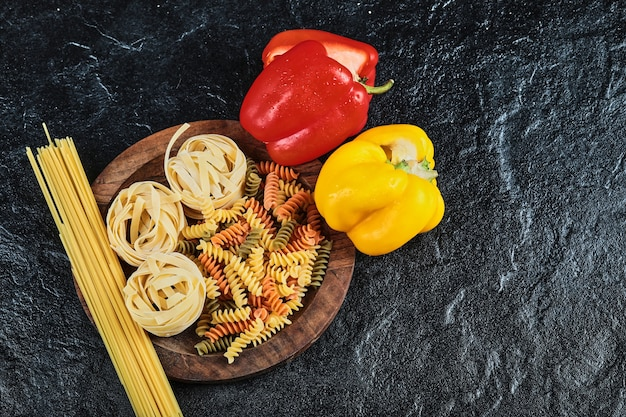 Plate of uncooked various pasta and peppers on dark table.