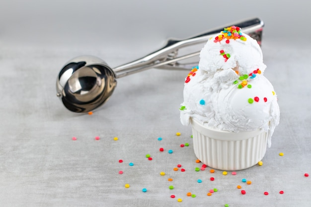 Plate of vanilla ice cream scoop swith sprinkles and waffle cones.