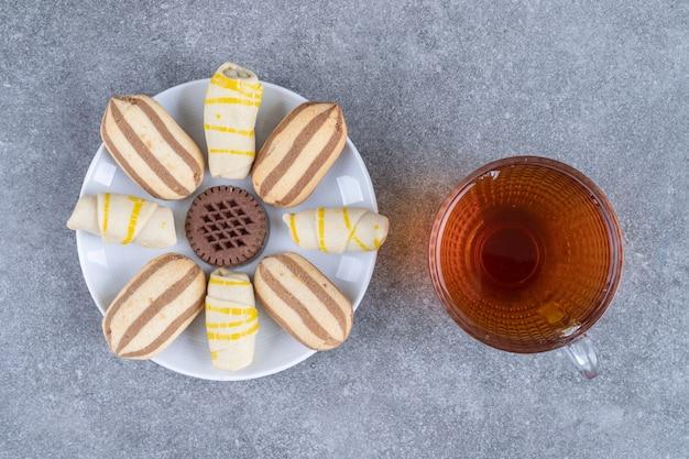 Piatto di vari biscotti e bicchiere di tè sulla superficie di marmo
