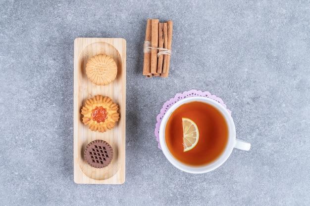 Piatto di vari biscotti con tazza di tè su superficie di marmo