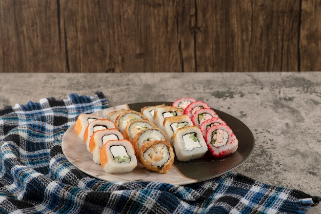 Plate of various delicious sushi rolls on marble table