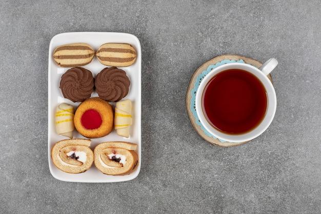 Piatto di vari dessert e tazza di tè su marmo.