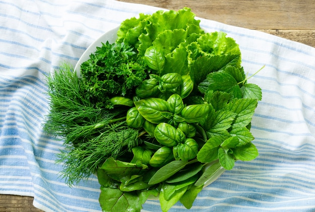 Plate of various fresh greens on a textile background