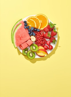Plate of various fruit and berries isolated on yellow background, top view