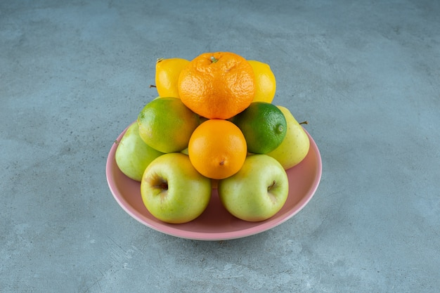 Un piatto di frutta varia, sullo sfondo marmoreo. foto di alta qualità