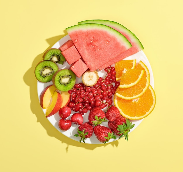 Plate of various fsliced colorful ruit and berries isolated on yellow background, top view