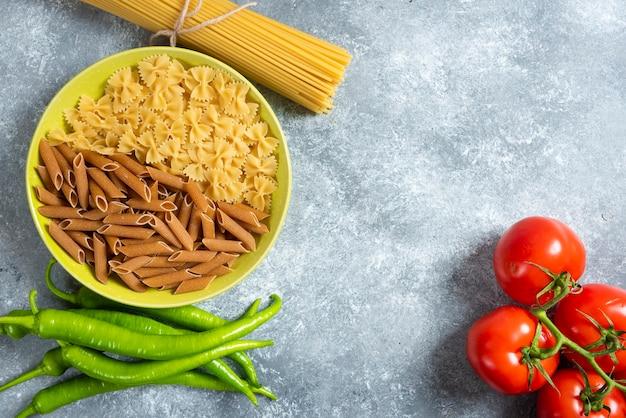 Piatto di vari tipi di pasta, peperoncino e pomodori su sfondo marmo.