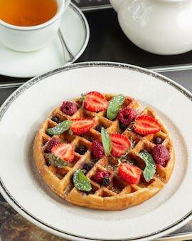 Plate of waffle topped with strawberries, raspberries, cranberries, and mint leaves