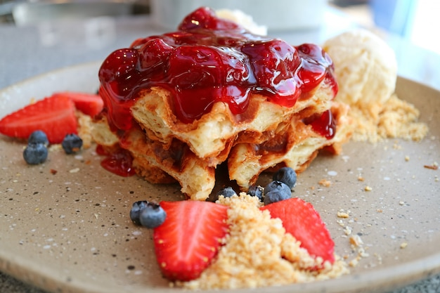 Plate of waffle with strawberry sauce, fresh berries and vanilla ice cream
