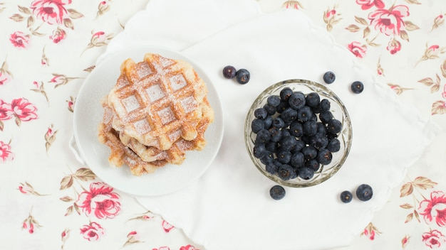 Plate of waffles and blueberries bowl on floral background