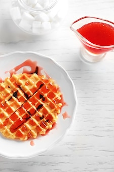 Plate of waffles with chocolate glaze on wooden background