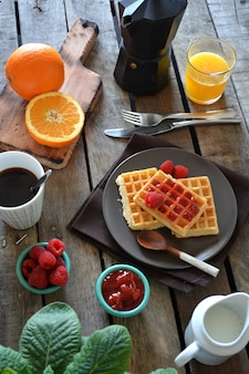 Plate of waffles with raspberry marmalade, orange juice and coffee