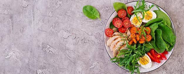 케토 다이어트 음식 접시. 체리 토마토, 닭 가슴살, 계란, 당근, arugula와 시금치 샐러드. 케토 점심. 평면도