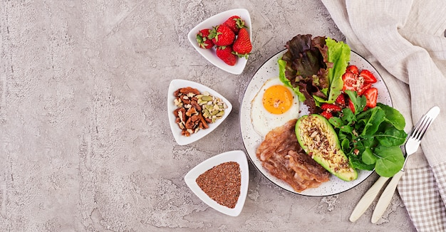 Тарелка с кето диетическое питание. жареные яйца, бекон, авокадо, руккола и клубника. кето завтрак. вид сверху