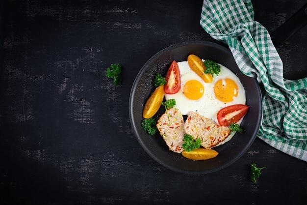 Тарелка с диетическим питанием кето. жареные яйца, мясной рулет и помидоры. кето, палео-завтрак. вид сверху, плоская планировка
