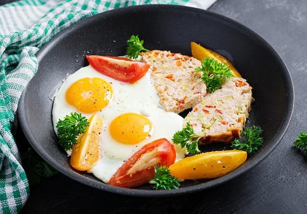 Тарелка с диетическим питанием кето. жареные яйца, мясной рулет и помидоры. кето, палео-завтрак