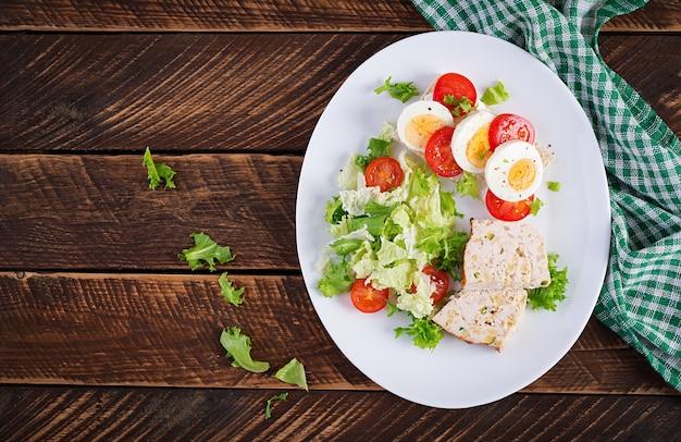Тарелка с диетическим питанием кето. бутерброд с вареным яйцом и помидорами. мясной рулет и салат. кето, палео-завтрак. вид сверху, плоская планировка