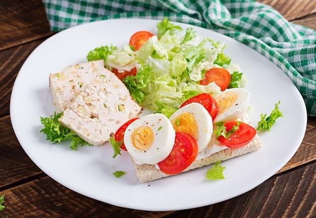 Тарелка с диетическим питанием кето. бутерброд с вареным яйцом и помидорами. мясной рулет и салат. кето, палео-завтрак.