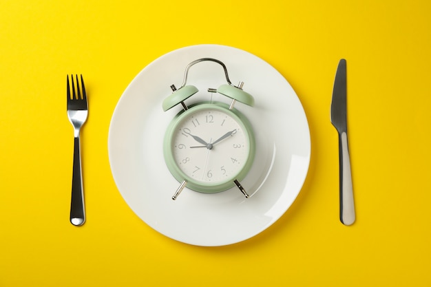 Plate with alarm clock, fork and knife on yellow
