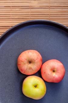 Тарелка с яблоками. осенний макет. фруктовые яблоки. осенняя картинка. яблоки и осенние листья