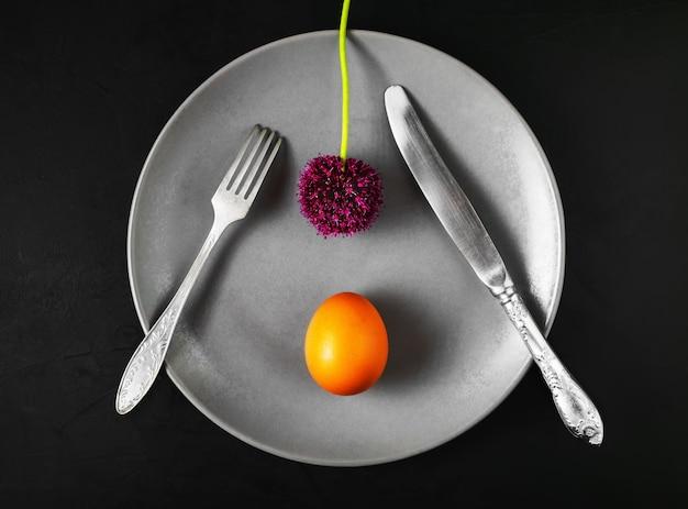 Тарелка с техникой, вареным яйцом и цветком черемши