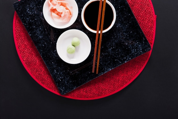 Plate with asian condiments and chopsticks