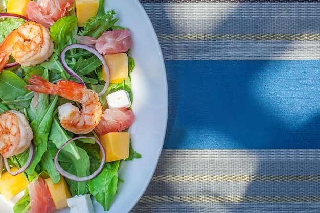 Plate with asian salad with shrimp, mango and pomelo