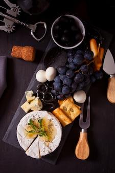 Тарелка с ассорти из сыров, фруктов и других закусок для вечеринки. вид сверху.