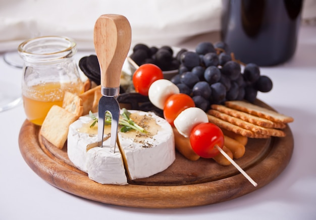 Plate with assorted cheese, fruit and other snacks for party.