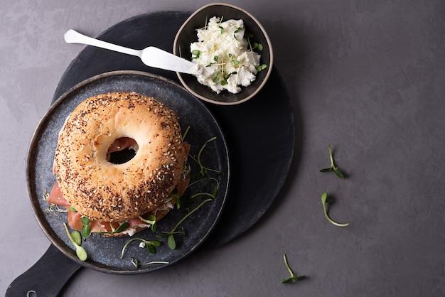 Тарелка с бубликом со сливочным сыром, сухой вяленой ветчиной и микрозеленью на сером фоне, концепция вкусной закуски.