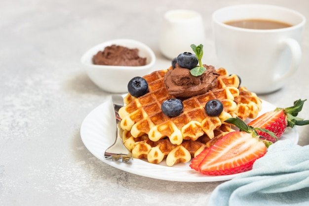 Plate with belgian waffles with chocolate sauce, berries and mint. breakfast or lunch.