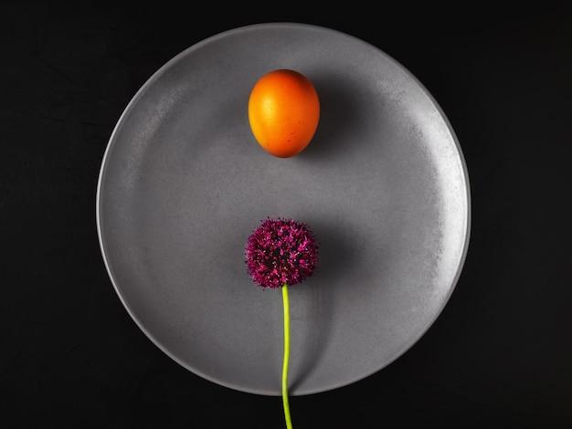 Тарелка с вареным яйцом и цветком черемши