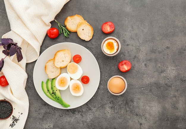 Plate with boiled eggs, bread and vegetables on grey
