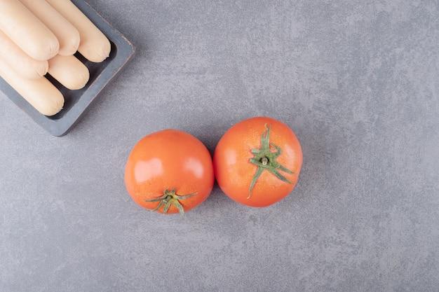 Un piatto con salsicce bollite e pomodori rossi