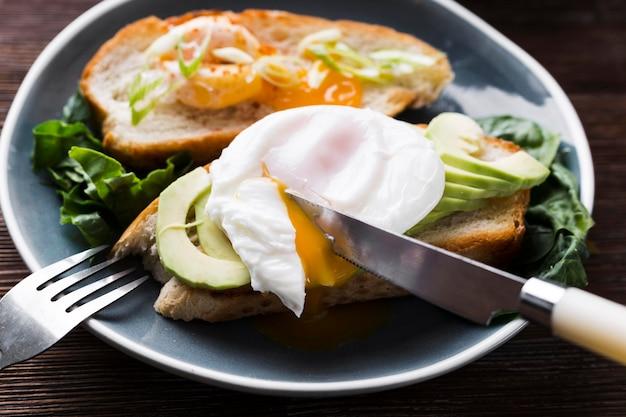 Тарелка с хлебом и жареным яйцом и авокадо