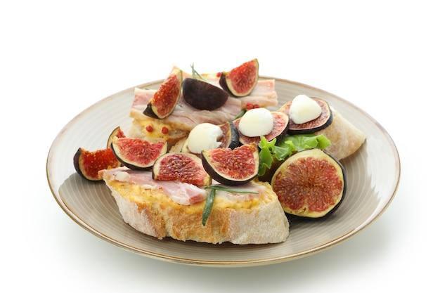 Тарелка с брускеттой с инжиром, изолированные на белом фоне