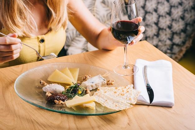 チーズを盛り付けます。背景にガラスの赤ワインを保持している女の子。クルミ、はちみつとおいしいチーズミックス。皿に盛り付けます。ワインの食べ物。