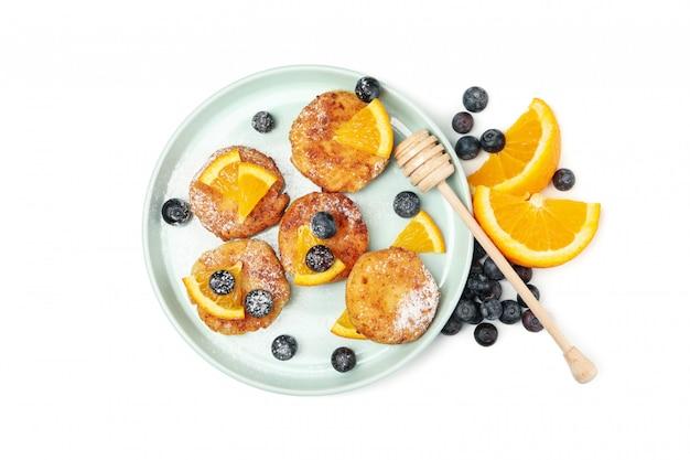 Тарелка с сырными блинами и фруктами, изолированные на белой поверхности