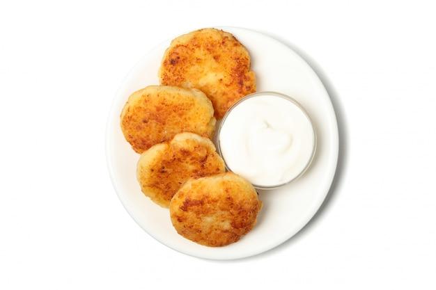 Тарелка с сырными блинами и сметаной на белой поверхности