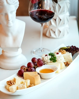 Plate with cheeses and a glass of red wine