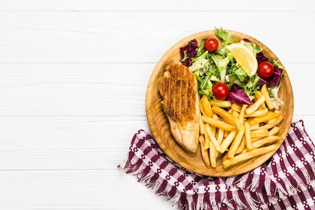 Тарелка с курицей и салатом возле салфетки