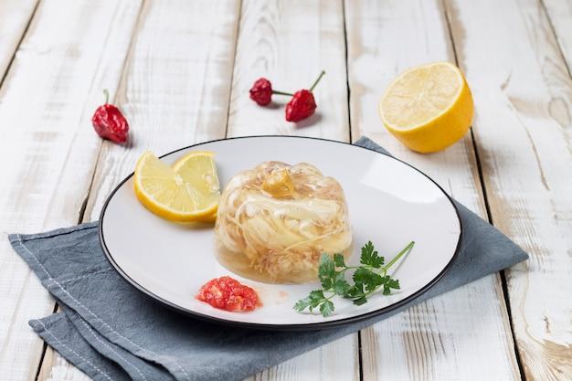 Тарелка с куриным киселем, украшенная дольками лимона, зеленью и специями.