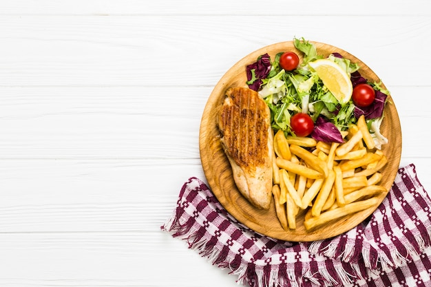 Plate with chicken and salad near napkin