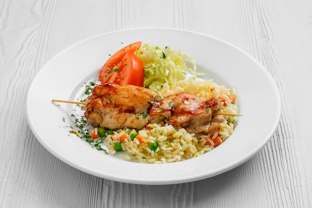 Plate with chicken shashlik, rice with peas and cabbage salad